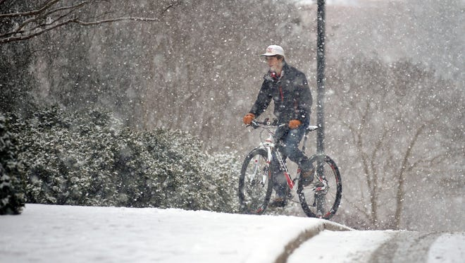 Daniel Trussell rides his bike as snow falls, Wednesday in Oxford.