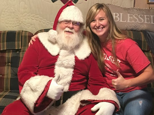 Laurie K. Blandford takes a photo with Santa Claus