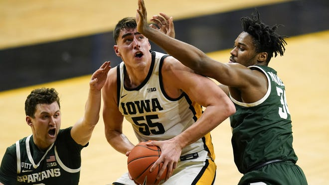 Iowa center Luka Garza (5) drives to the basket between Michigan State guard Foster Loyer, left, and forward Julius Marble II, right, during the second half of an NCAA college basketball game, Tuesday, Feb. 2, 2021, in Iowa City, Iowa. Iowa won 84-78.