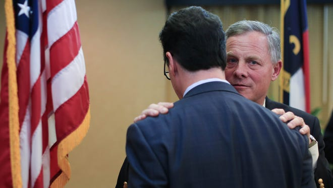 Republican U.S. Senator Richard Burr greets an unidentified man during a reception held prior to the Buncombe County Republican Party's Lincoln Reagan Dinner last month.