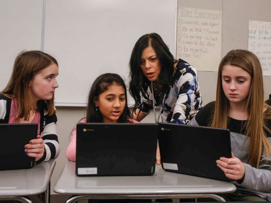 Julie Young, a substitute teacher in Fort Dodge, works with seventh-grade students in reading class on Tuesday, Jan. 30, 2018.