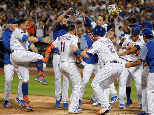 New York Mets' Jose Bautista (11) is mobbed at the