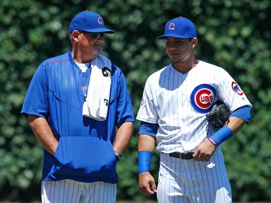 Chicago Cubs pitching coach Chris Bosio, left, talks with catcher Willson Contreras before a baseball game against the Pittsburgh Pirates, Friday, June 17, 2015, in Chicago. (AP Photo/Nam Y. Huh)