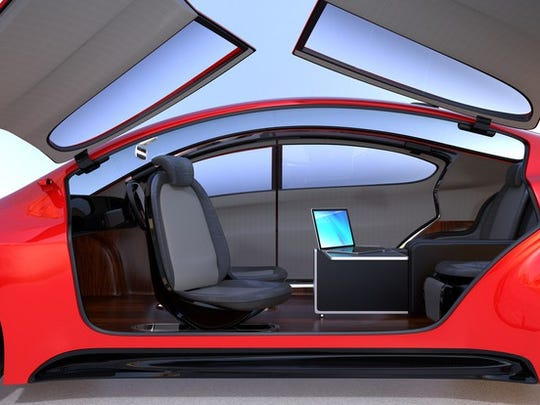 A side view of a red sports car with gull doors opened upward showing an interior with seats facing one another. There is no driving apparatus, implying that this is a fully autonomous car.