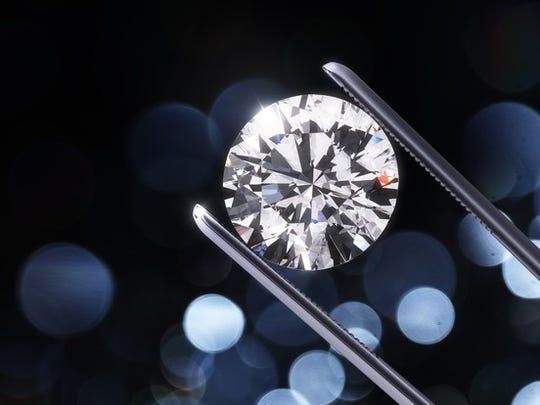 Top of a diamond being held by tweezers
