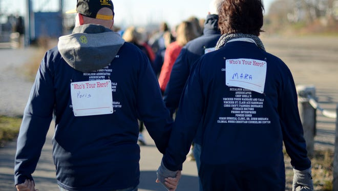 Participants Nick and Becky Feddes, of Point Edward, ON, hold hands and support their heroes, the city of Paris, and Mara McCalmon, formerly Skinner, Sunday, Nov. 15, during the You're My Hero 5K run at Vantage Point.