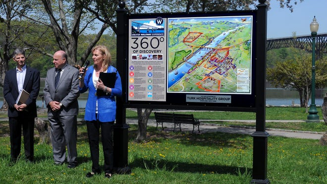 Walkway Over the Hudson Executive Director Elizabeth Waldstein-Hart discusses the unveiling of one of 14 Greater Walkway Experience Gateway signs located in the City of Poughkeepsie and Town of Lloyd during a press conference Monday at Waryas Park in Poughkeepsie. Standing next to Waldstein-Hart are Steve Rosenberg, senior vice president of Scenic Hudson, far left, and Charles North, president and chief executive officer of the Dutchess County Regional Chamber of Commerce. The Walkway is pictured in the background.
