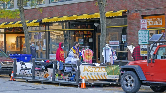 "AS220 sets up a ""parklet"" on Saturday outside its place on Empire Street, which it uses to show and sell art and crafts. This is part of Providence's program to let businesses take over two on-street metered spaces in front of their shops."