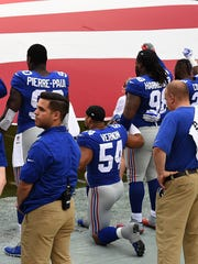 New York Giants defensive end Olivier Vernon (54) kneels during the national anthem before the start of the game against the Tampa Bay Buccaneers at Raymond James Stadium on Sunday.