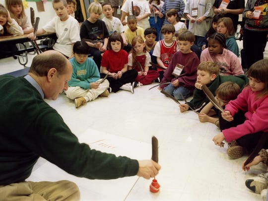 Lincoln Elementary School third-graders gather around calligrapher Donald Jackson in January 1998 as he demonstrates the traditional technique of drawing letters with a quill.