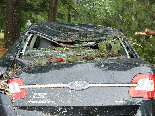 A car sustained severe damage from a tree falling on
