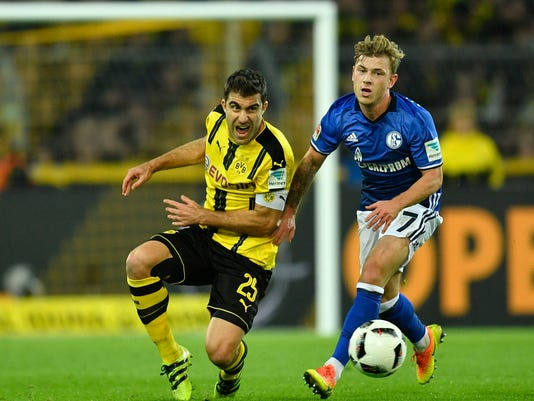 FILE- In this Saturday, Oct. 29, 2016 file photo, Dortmund's Socratis, left, and Schalke's Max Meyer challenge for the ball during the German Bundesliga soccer match between Borussia Dortmund and FC Schalke 04 in Dortmund, Germany. Schalke can settle its angst over an inconsistent season so far with a win over Borussia Dortmund in the 172nd Ruhr derby on Saturday. (AP Photo/Martin Meissner, File)