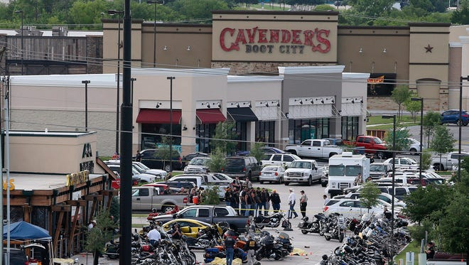 """FILE - In this May 17, 2015, file photo, authorities investigate a shooting in the parking lot of Twin Peaks restaurant in Waco, Texas. Prosecutors have dismissed another 42 cases relating to the 2015 shooting in Waco involving rival biker gangs that left nine dead and 20 others injured. McLennan County prosecutors said Tuesday, May 8, 2018, they're dismissing the cases while focusing on """"more culpable"""" defendants. (AP Photo/Jerry Larson, File)"""