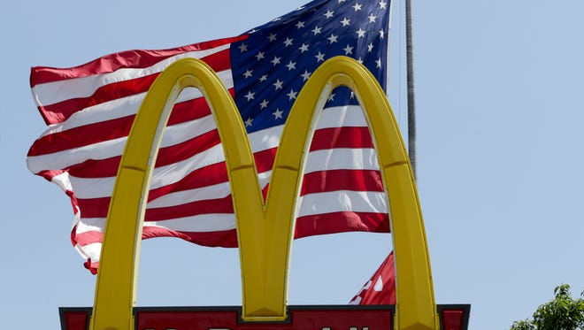 A flag flies behind the golden arches of a McDonald's restaurant in La Vista, Neb., Friday, May 25, 2018.