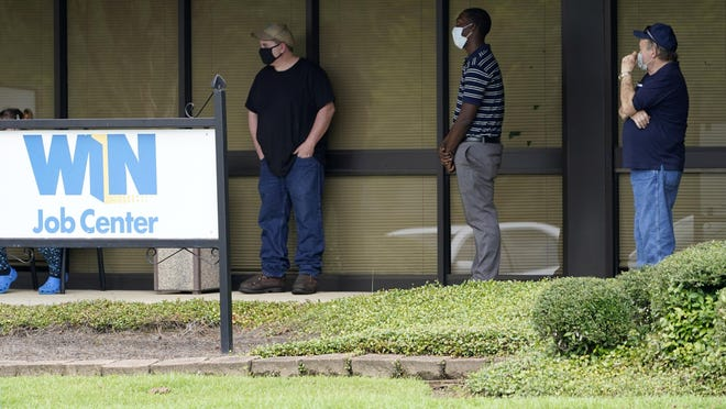 FILE - In this Aug. 31, 2020, file photo, clients line up outside the Mississippi Department of Employment Security WIN Job Center in Pearl, Miss. The government issues the jobs report Friday, Sept. 4, for August at a time of continuing layoffs and high unemployment.