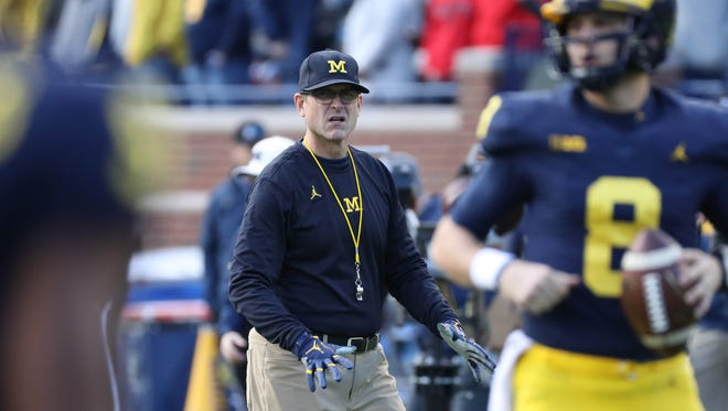 Michigan coach Jim Harbaugh watches his players go through drills before action against Ohio State last season.