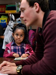 Alayna Rodriguez listens to Noah Watson during a reading exercise in a kindergarten class at Reagan Elementary School April 28.