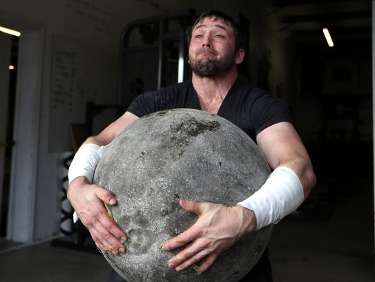 Brett Fain lifts a 350 pound stone as a part of his