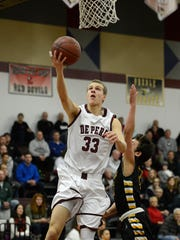 De Pere's Zack Rabas (33) lays up a shot during a basketball