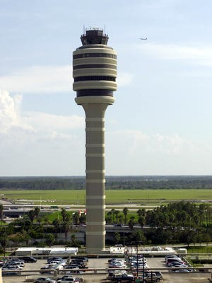 The new control tower at Orlando International Airport towers over the cars atop the roof of the parking lot in Orlando, Fla., Monday Sept. 16, 2002.