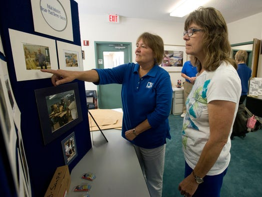 ARC Gateway employee Carol Hicks, left, explains to Sally Severson, right, all the things the organization's clients do in the community during an open house at the center Tuesday morning. ARC Gateway is celebrating its 60th year in operation.