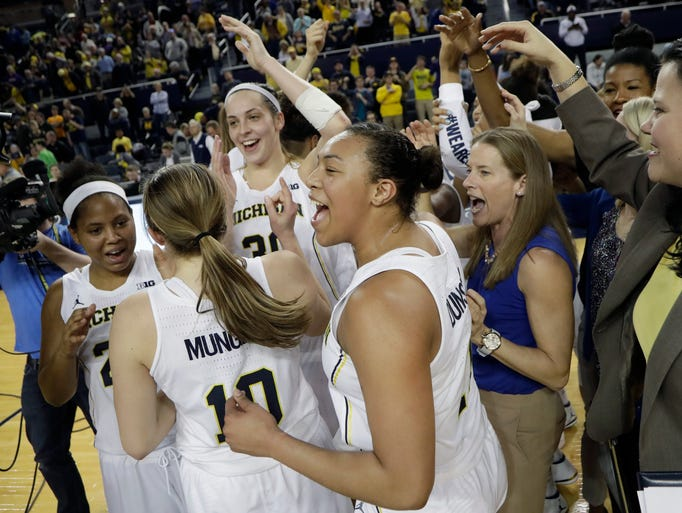 The University of Michigan celebrates its 65-61 win