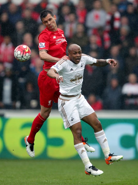 Swansea City's Andre Ayew, right, and Liverpool's Dejan Lovren battle for the ball during the English Premier League soccer match between Swansea City and Liverpool,  at the Liberty Stadium, in Swansea, Wales,  Sunday May 1, 2016. (David Davies/PA via AP) UNITED KINGDOM OUT