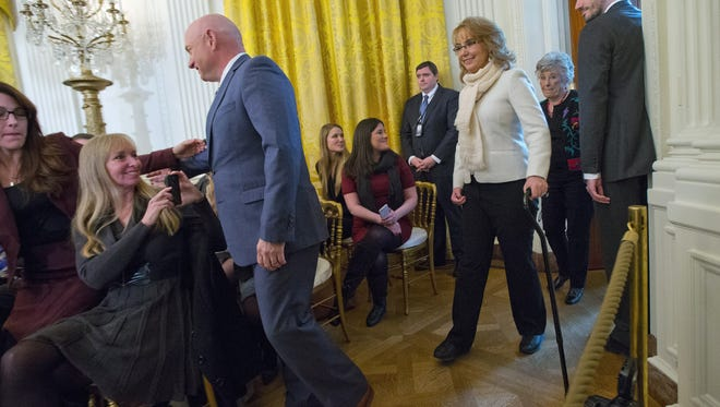 Former Arizona Rep.  Gabby Giffords and her husband Mark Kelly, left, arrive in the East Room of the White House in Washington, Tuesday, Jan. 5, 2016, to listens to President Barack Obama speak about steps his administration is taking to reduce gun violence. Also on stage are stakeholders, and individuals whose lives have been impacted by the gun violence. (AP Photo/Pablo Martinez Monsivais)