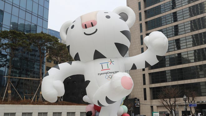 "People walk by an official mascot of the 2018 Pyeongchang Olympic Winter Games, white tiger ""Soohorang"" in downtown Seoul, South Korea, on Dec. 29, 2017."