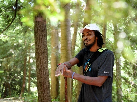 "Daniel White, also known by his trail name, the ""Blackalachian,"" leads a walk through the botanical garden at UNC Asheville July 12, 2018."