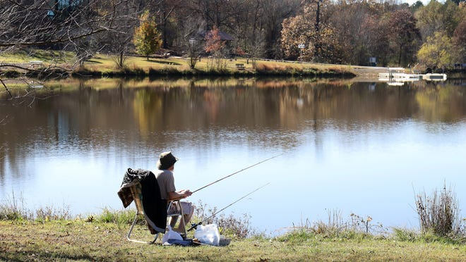 Timothy Beck of Greenwood, takes advantage of the warm weather, Monday, Nov. 16, spending the morning fishing at Wells Lake in Chaffee Crossing.