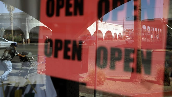 In this June 30 photo, a man passes a clothing shop with open signs in the window in Calexico, Calif. Records obtained by The Associated Press show governors working closely with business interests as they weighed when and how to reopen their economies during the coronavirus pandemic.