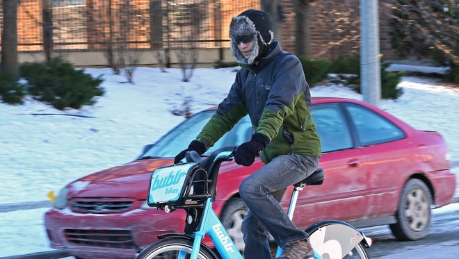 Wayne Wu rides a Bublr bike he picked at the Bublr station at East Pointe Market Place near his home in Milwaukee on Sunday. Wu topped the leaderboard in terms of miles ridden in 2017 by Bublr Bike customers, logging in 1,546.80 miles.