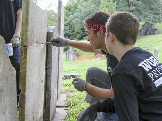 Randy Ruth, rear, shows Alexis LaPage, 16, how to repair