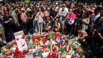 People pay tribute to victims outside the Liceu Theatre, on the site of a deadly van attack in Barcelona, Spain, on August 18, 2017.