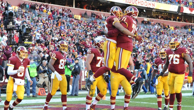 Dec 20, 2015; Landover, MD, USA; Washington Redskins tight end Jordan Reed (86) celebrates with tackle Trent Williams (71) after scoring a touchdown against the Buffalo Bills during the first half at FedEx Field. Mandatory Credit: Brad Mills-USA TODAY Sports
