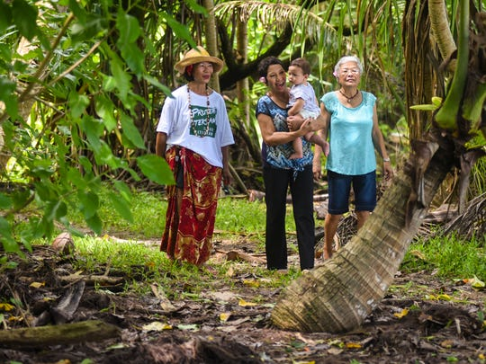 In this Aug. 31, 2017 file photo, Lou Flores Bejado, center, carries her grandson, Camden, as they stroll through the jungles of Litekyan with her sister, Theresa Bejado Nellis, left, and cousin, Catherine Flores McCollum.