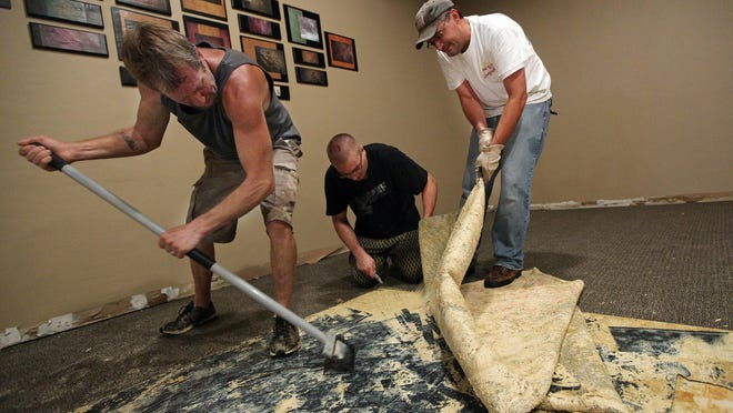 Dave Dixon (left to right), Jake Rinehart and Darin Glanzer tear out wet carpet at Christ Community Church after flooding in August. Elsewhere, the city has offered to buy homes in the area of S. Covell Avenue to help prevent flooding in the center of the city.