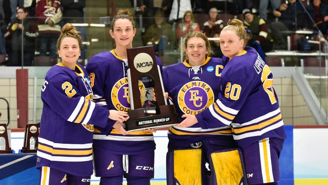 Elmira College players hold their runner-up trophy after a 2-1 loss to Norwich on Saturday in the NCAA Division III championship game in Northfield, Vermont.
