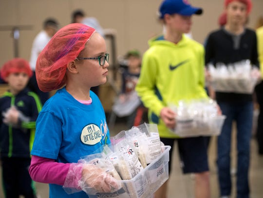 Natalie Paul carries bags of rice during Concord United