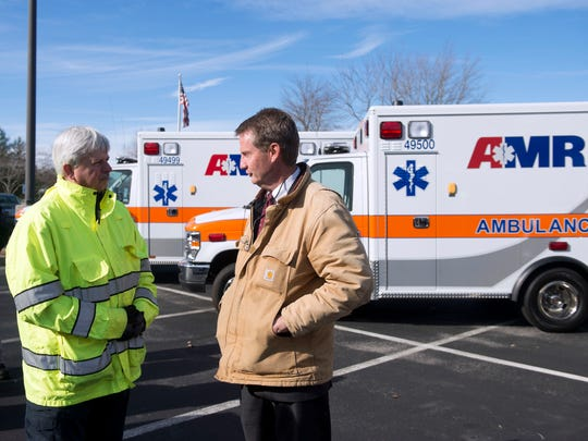 Knox County Mayor Tim Burchett, right, talks with Rural Metro Fire Chief Jerry Harnish during a news conference announcing the rebranding of Rural Metro ambulances to AMR on Thursday, Dec. 8, 2016.