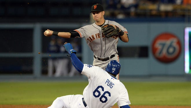 San Francisco Giants second baseman Joe Panik throws to first as Los Angeles Dodgers right fielder Yasiel Puig is out on a double play in the 11th inning of the game at Dodger Stadium on Sept. 22