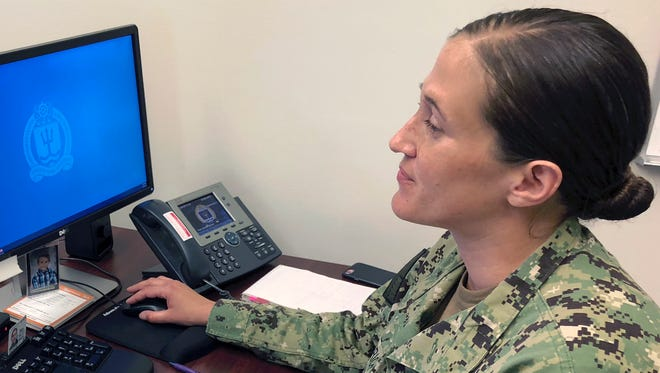 U.S. Navy Legalman First Class Tamatha Schulmerich works at her desk at the Naval War College  in Newport, R.I. The Navy said Tuesday it will let women sailors sport ponytails and other longer hairstyles, reversing a policy that long forbade females from letting their hair down.