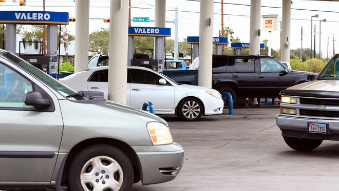Vehicles gas up after a gas station opened its business after it shut down by Hurricane Harvey on Sunday, Aug. 27, 2017, in Corpus Christi, Texas.