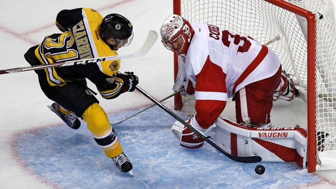 Detroit Red Wings goalie Jared Coreau, right, makes a pad save on a shot by Boston Bruins center Austin Czarnik on Sept. 28, 2016.