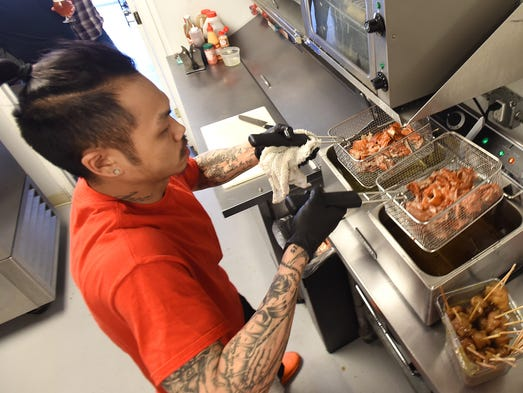 Chef Justin Yuen, co-owner of Chino Loco, fries duck