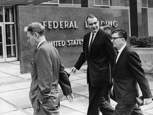 11:45 a.m. Wednesday, April 3, 1968 - Fire and Police Director Frank Holloman (left),  Mayor Henry Loeb (center) and unidentified man head to the Federal Building. Federal Judge Bailey Brown, at the request of Loeb and other city officials, issued a temporary order restraining Dr. Martin Luther King Jr. or any of his followers from leading a march in Memphis.