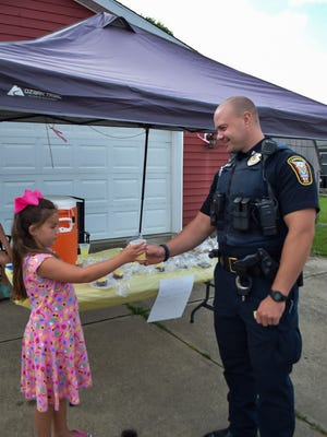 Valynn Johnson, of Cambridge,delivers a cup of lemonade to Sgt. Warner of the Cambridge Police Department. Valynn is raising money to help out the dog shelter