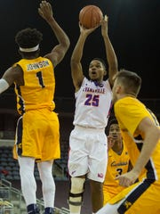 University of Evansville's Duane Gibson (25) shoots over Canisius College's Malik Johnson (1) as the University of Evansville Purple Aces take on the Canisius Golden Griffins at the Ford Center in Evansville, Ind., on Saturday, Dec. 9, 2017.