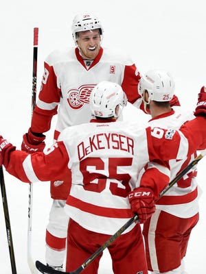 Red Wings forward Anthony Mantha, top, Danny DeKeyser (65) and Mike Green, right, celebrate after Green scored a goal in Nashville.